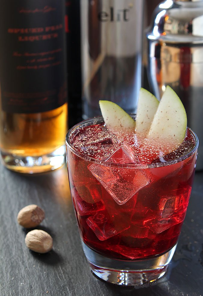 Vodka, Red Wine and Spiced Pear Liqueur Cocktail Garnished with Pear Slices and Nutmeg