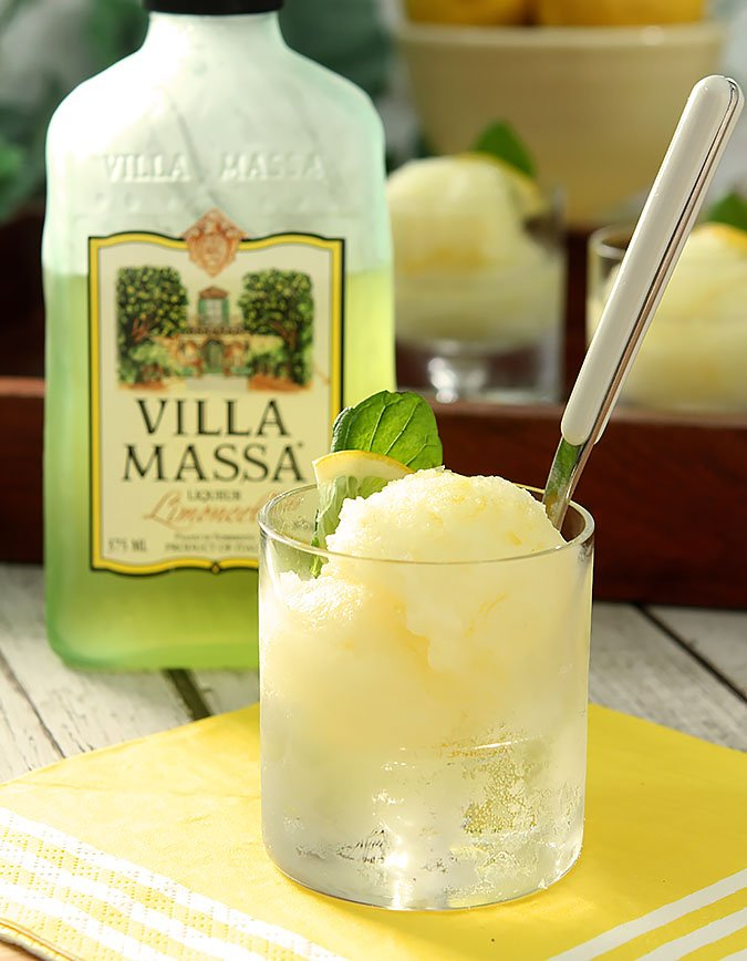 Limoncello Sorbet Served in a short glass with mint and lemon and a spoon.