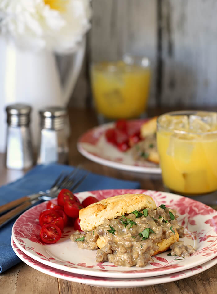 Tabletop Setting of Biscuits with Sausage and Maple Flavor White Gravy with Cherry Tomatoes and Glasses of Orange Juice