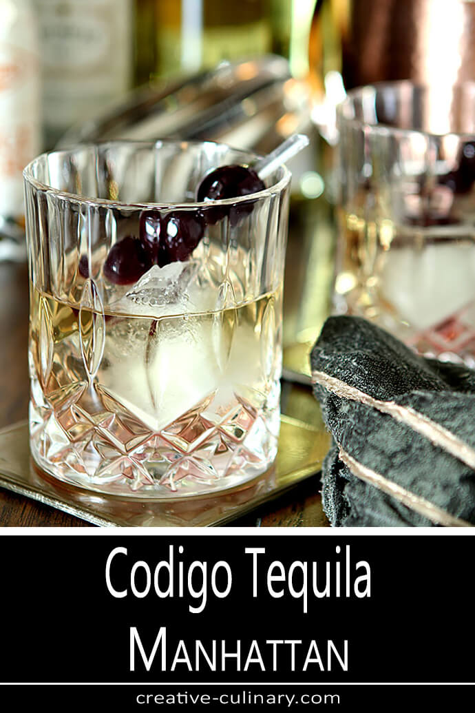 Codigo Tequila Manhattan Served in a Decorative Crystal Glass and Garnished with Burgundy Cherries