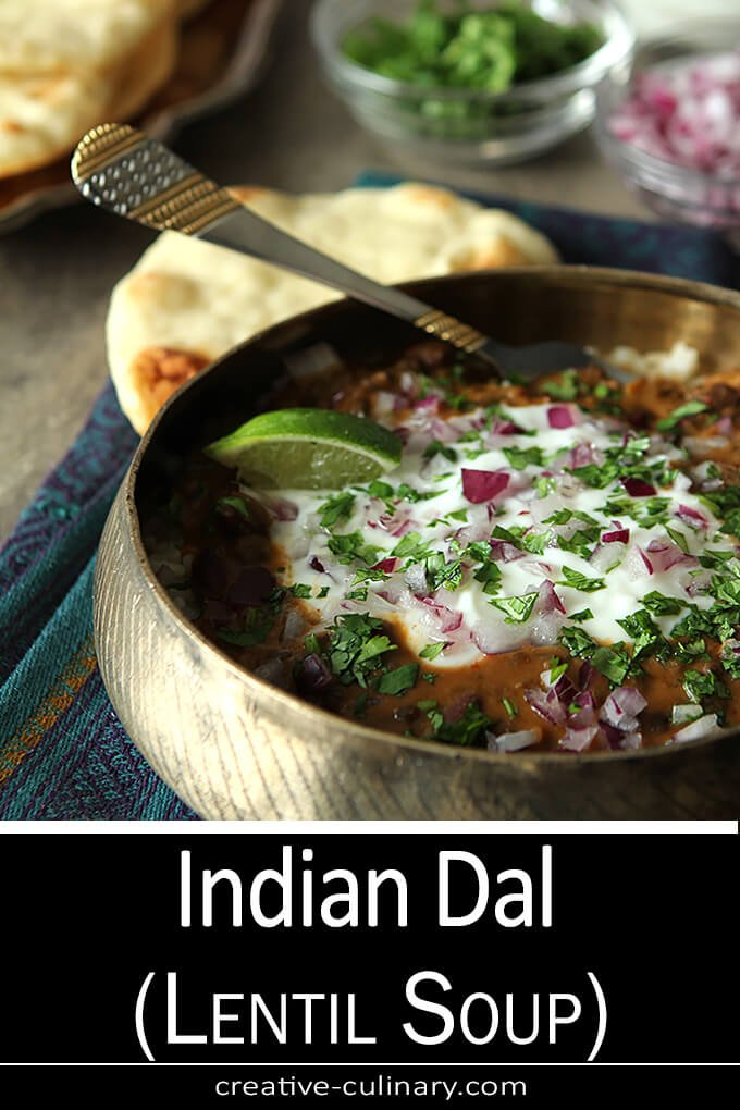 Dal Makhani an Indian Lentil Stew is Served in a Metal Indian Bowl and Topped with Yogurt, Red Onion, and Cilantro
