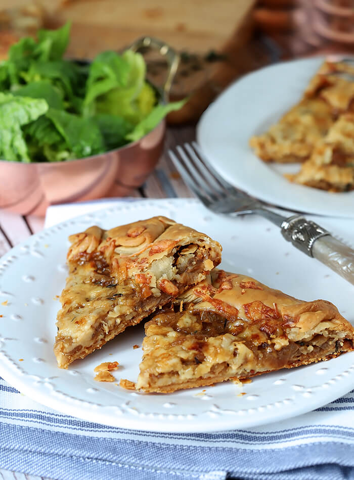 French Onion Galette Slices on a White Plate Served with a Salad