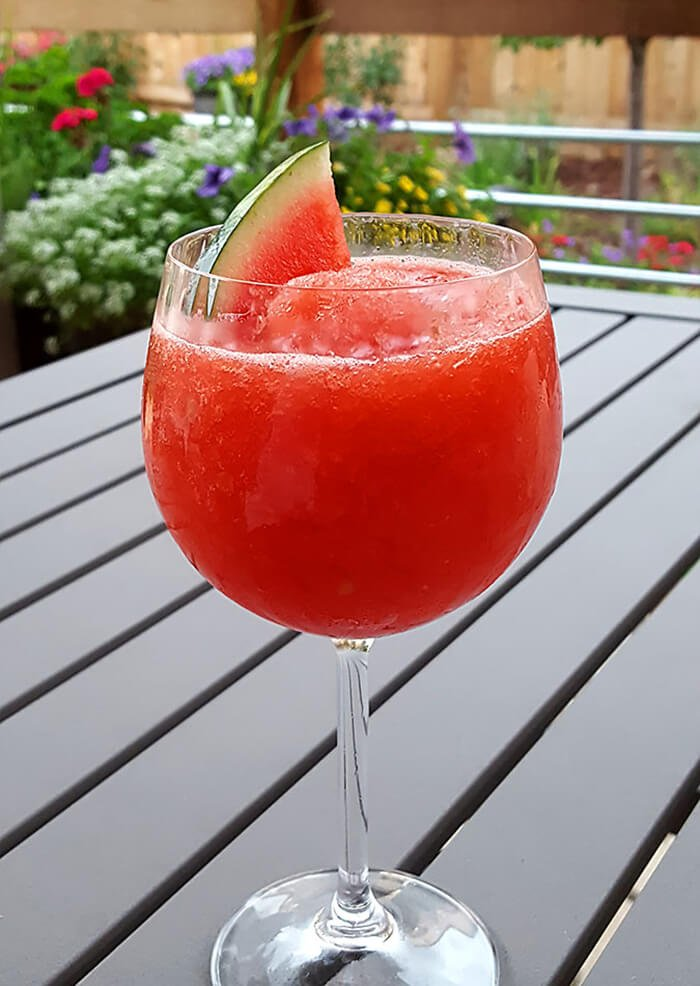 Fresh Watermelon Frosé in a Wine Glass and Garnished with a Watermelon Slice