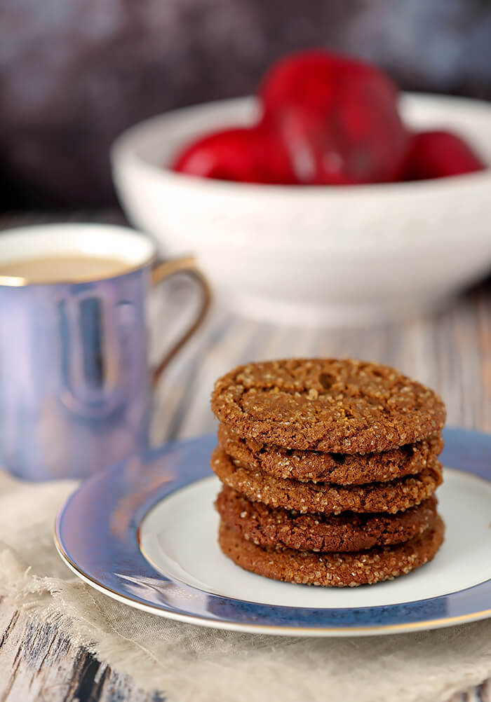 Molasses Cookies on a Blue and White Plate with Apples in the Background