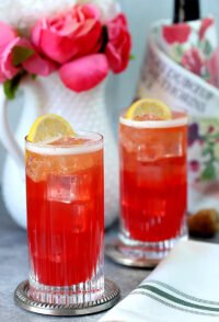 Sparkling Raspberry, Vodka, and Honey Cocktail Served in Two Highball Glasses and Garnished with Lemon