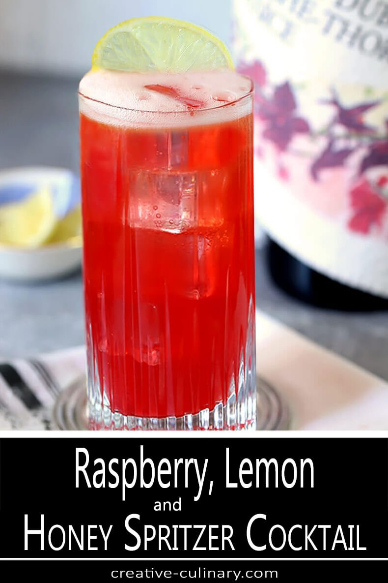 Tom Collins Glass with Sparkling Raspberry, Vodka, and Honey Cocktail Garnished with a Lemon Slice