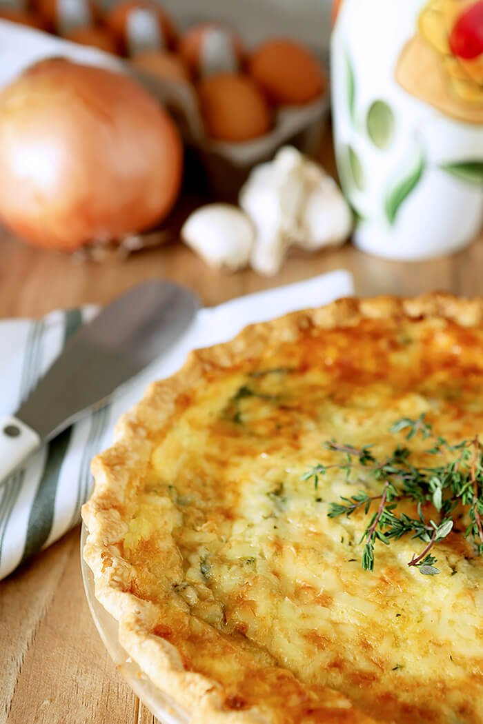 Spinach, Onion, and Mushroom Quiche in a White Pie Plate on a Table with a Green and White Napkin and a Serving Knife.