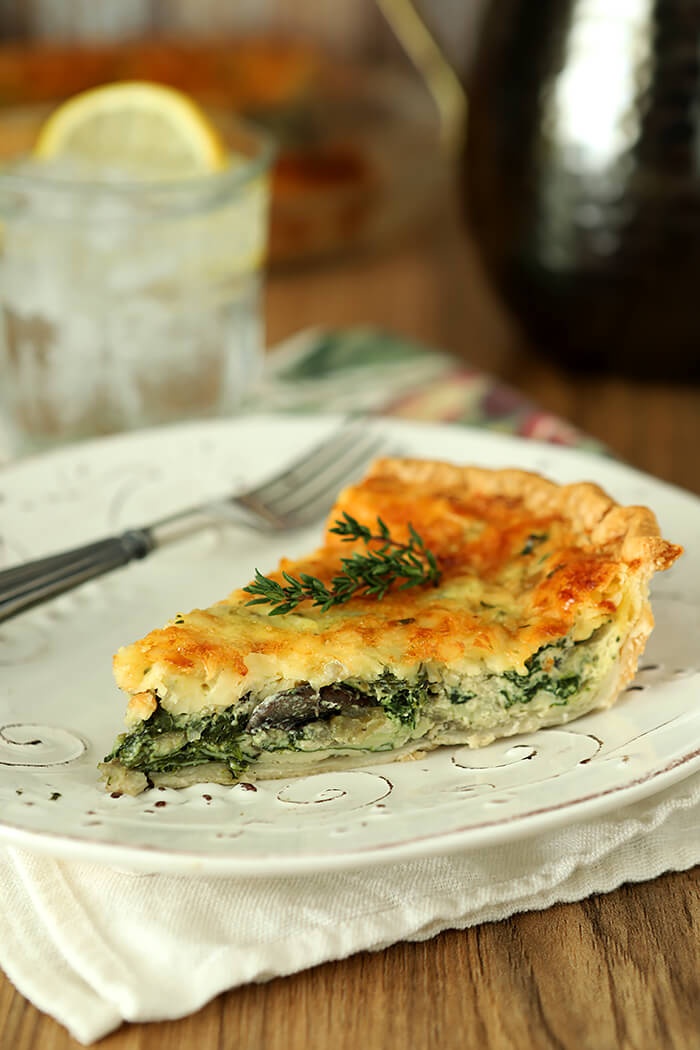 Spinach, Onion, and Mushroom Quiche with White Cheddar Cheese Sliced and Served on a White Plate with Thyme Garnish