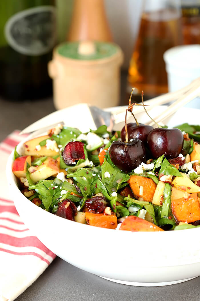 Sweet Potato and Spinach Salad with Pecans, Cherries and Goat Cheese Served in a White Bowl and Whole Cherries for Garnish