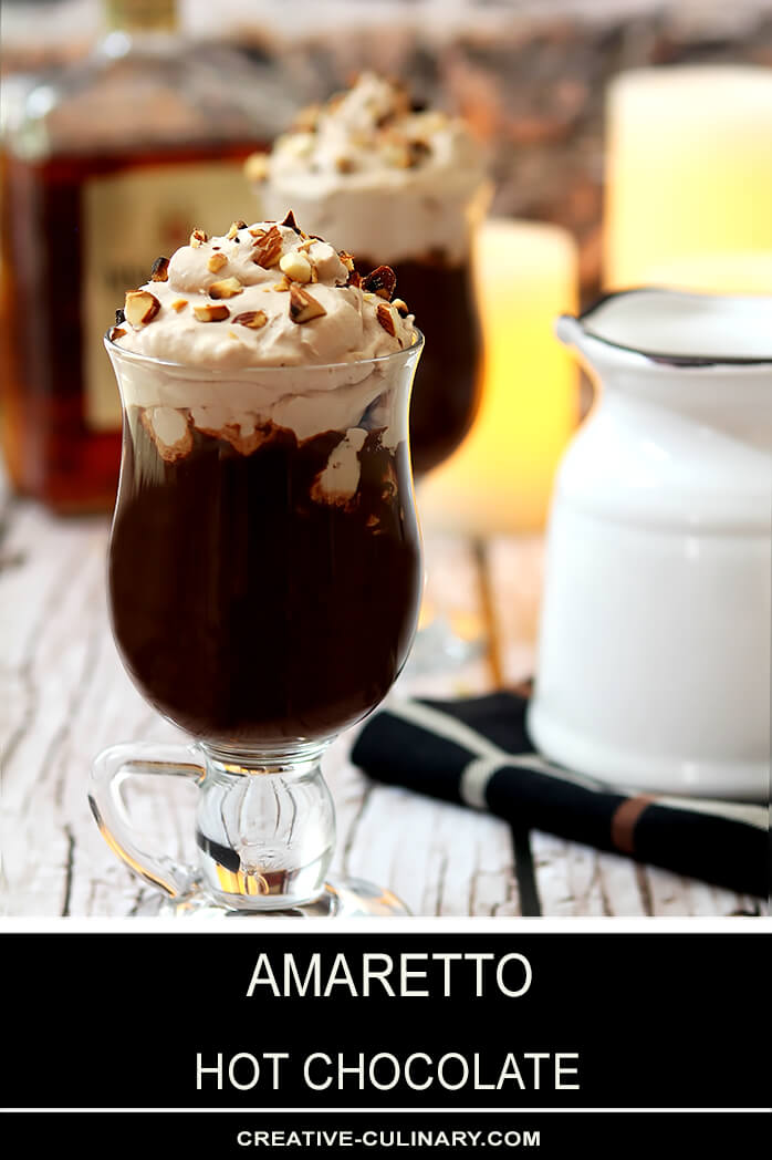Amaretto Hot Chocolate in a Glass Mug with Whipped Cream and Toasted Almonds for Garnish
