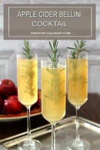 Apple Cider Bellini Cocktail in Champagne Glass Garnished with Sprig of Rosemary