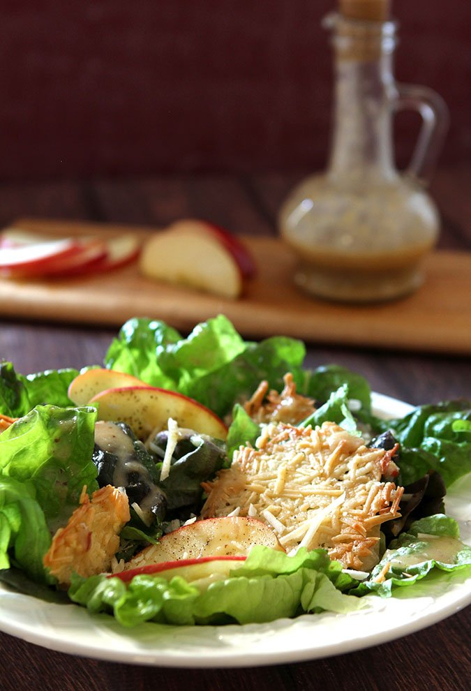 Red Leaf Lettuce and Apple Salad with Parmesan Crisps on a White Plate