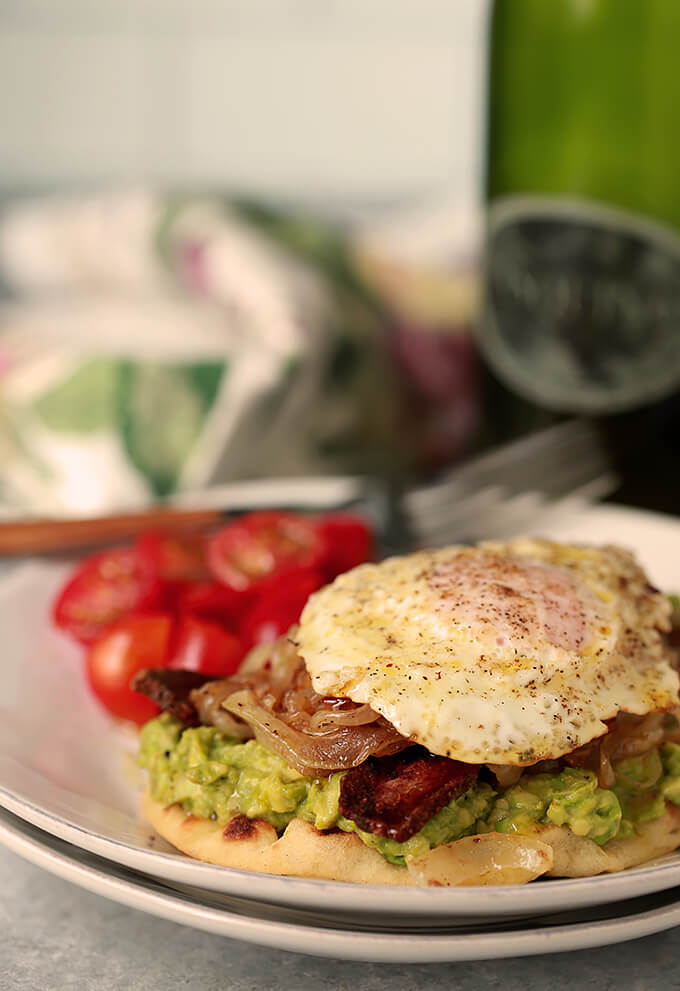 Avocado Toast with Bacon and Egg on Naan Served with Cherry Tomatoes on a White Plate