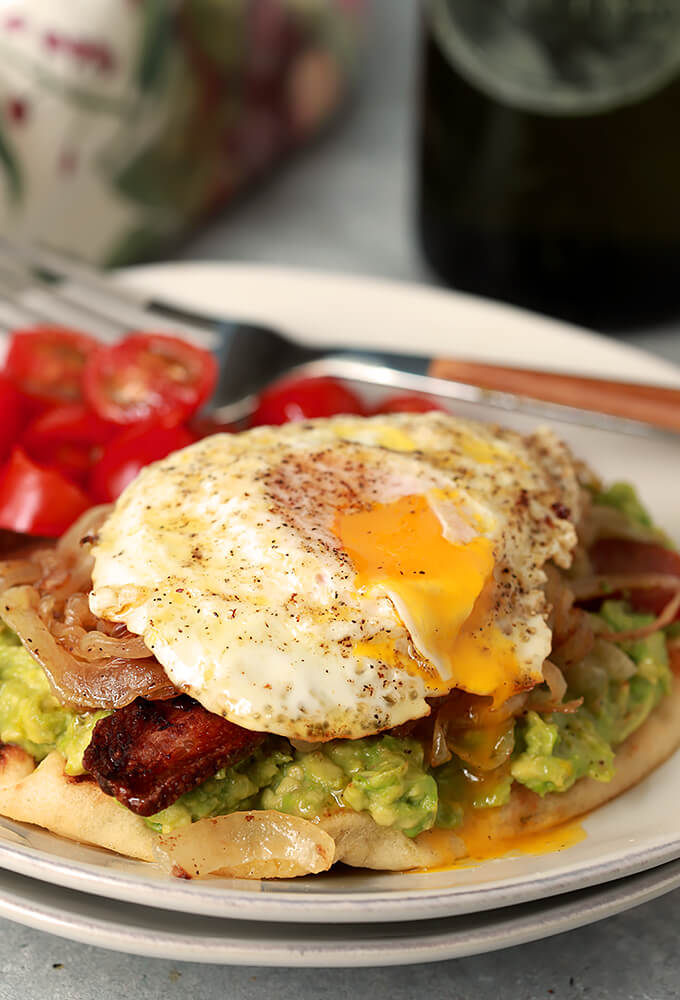 Avocado Toast with Bacon and Egg on Naan Served on a White Plate with Cherry Tomatoes