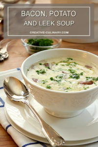 Bacon, Potato, and Leek Soup In White Bowl Garnished with Parsley