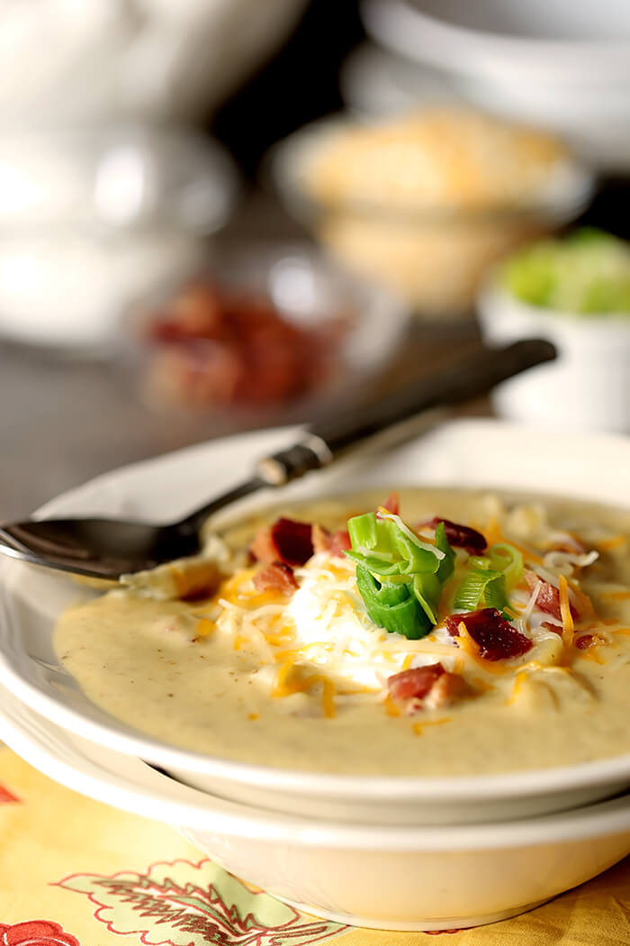 Baked Potato Soup with Leeks Garnished with Sour Cream, Leeks, and Bacon Bits