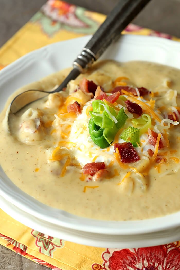 Baked Potato Soup with Leeks in a White Bowl and Garnished with Sour Cream, Cheese, Bacon Bits and Sauteed Leeks