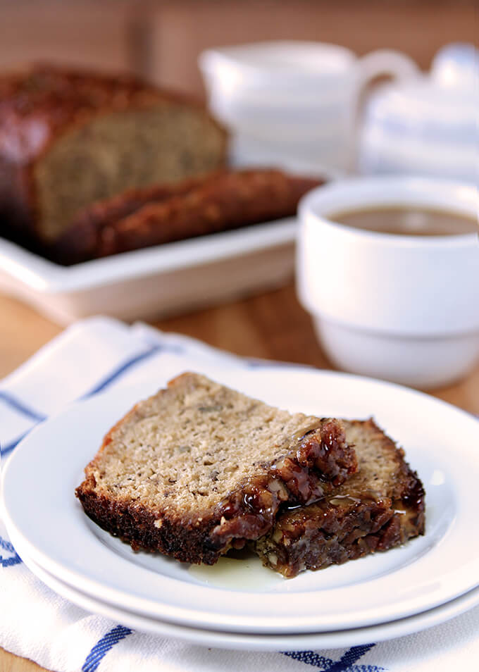 Banana Bread with Pecans and Toffee Glaze Sliced and Served on a White Plate with White and Blue Stiped Napkin