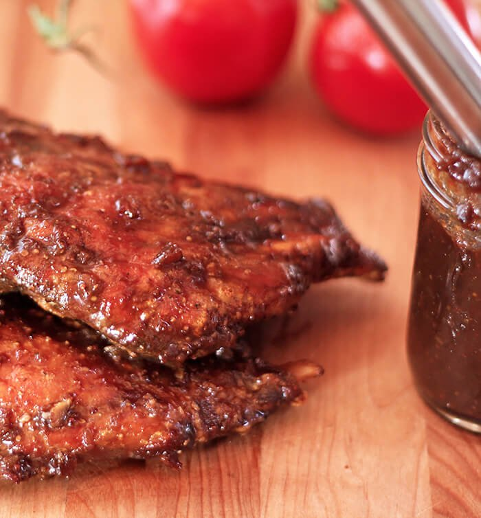 Smoked Ribs with Espresso Barbecue Sauce on Butcher Block with Tomatoes and Jar of Sauce