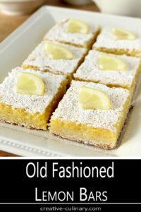 The Best Lemon Bars Served on a Rectangular Plate with Mini Lemon Wedges for Garnish
