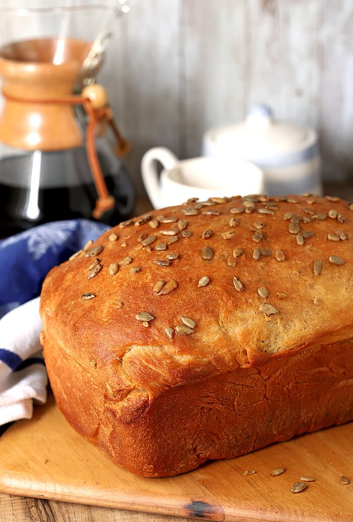 The Perfect White Bread with Milk and Honey Topped with Sunflower Seeds and Served on a Cutting Board