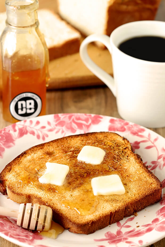 Slice of Billowy Off-White Bread with Milk and Honey Topped with Sesame Seeds and Served with Pats of Butter and Drizzled Honey