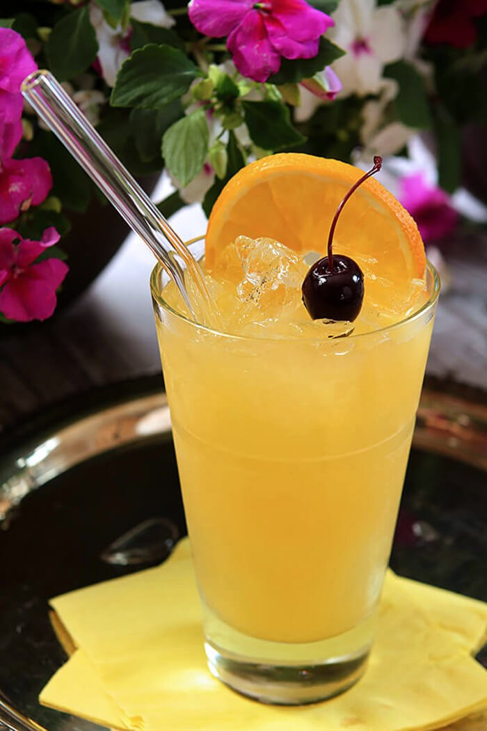 The Black-Eyed Susan Cocktail Served in a Tall Glass with Orange and Cherry Garnish