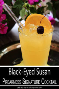 The Black-Eyed Susan - Preakness Signature Cocktail Served in a Tall Glass with a Cherry Garnish and a Straw
