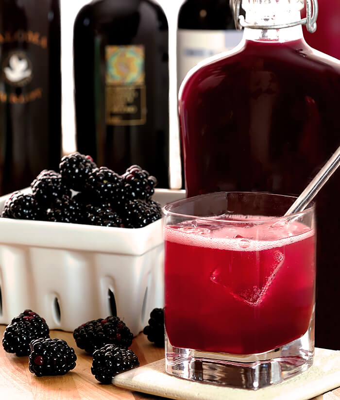 Homemade Blackberry Liqueur (Creme de Mure) in a flask bottle with fresh blackberries on display and a simple cocktail.