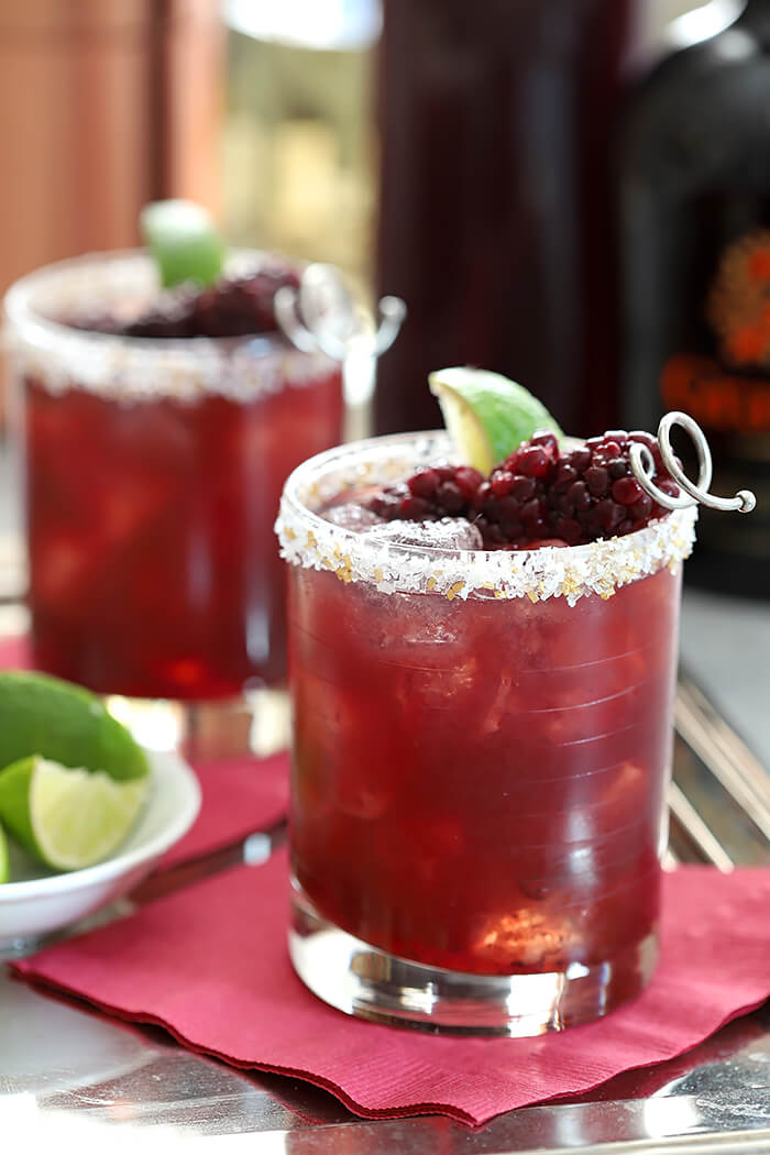 Blackberry Serrano Margaritas Served in Lowball Glasses with Sugar Crystals on Rim and Garnished with Blackberries and Lime Wedge
