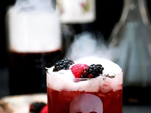 Sparkling Blackberry Smash Halloween Cocktail Served in a Glass with an Etched Skull and Dry Ice