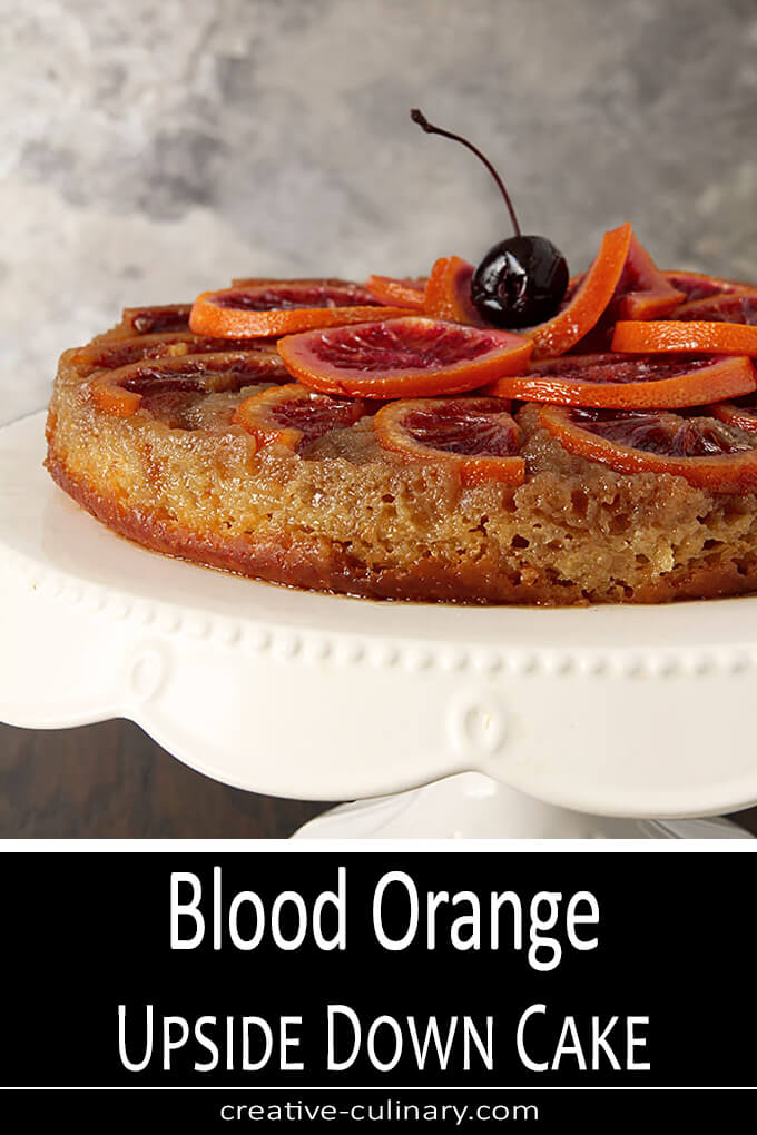 Blood Orange Upside Down Cake on a White Cake Plate with Blood Orange Slices for Garnish