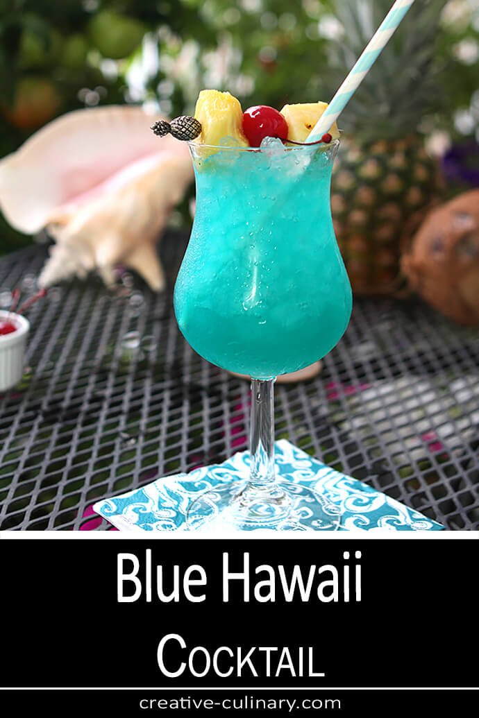 Blue Hawaii Cocktail served in a cocktail glass with both pineapple chunks and cherries for garnish.