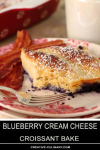 Slice of Blueberry Cream Cheese Croissant Bake White and Rose Plate with Bite Removed and Fork on Plate