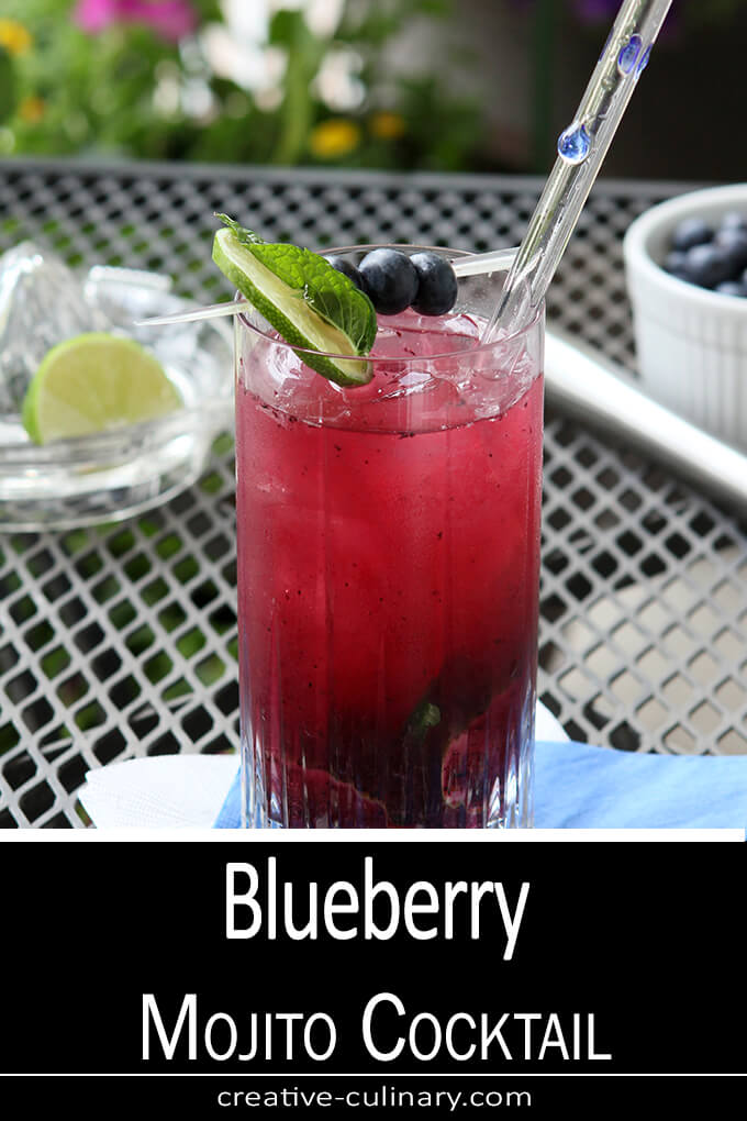 Blueberry Mojito Cocktail Served in a Tall Glass, Garnished with Lime and Blueberries and Served with a tall glass straw.