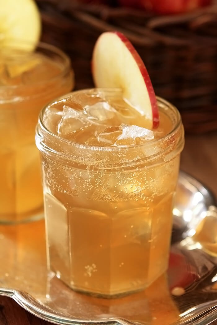 One Jelly Jar Glass of Bourbon and Apple Cider Cocktail with Ginger Beer Garnished with an Apple Slice