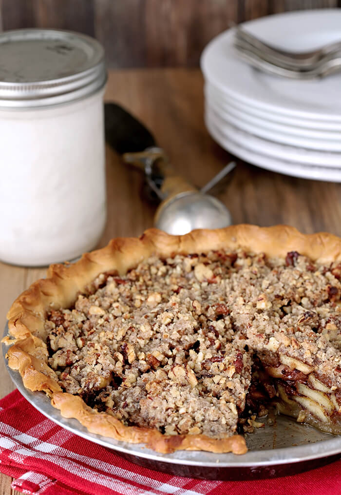 Bourbon Caramel Apple Pie with Pecan Crumble in a Metal Pie Plate with One Slice Missing