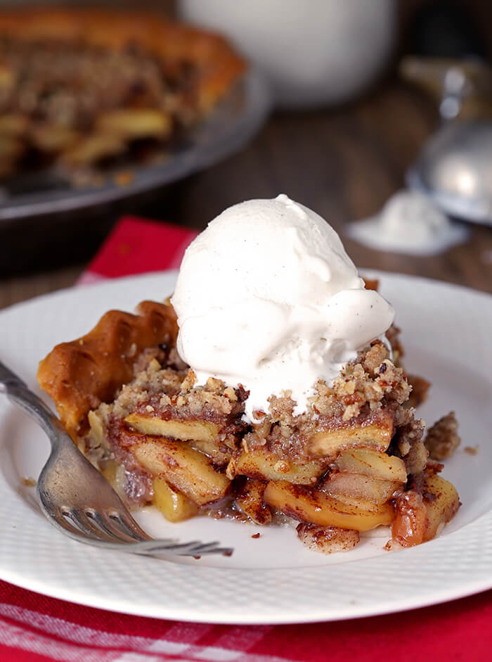 Closeup of Bourbon Caramel Apple Pie with Pecan Crumble with Vanilla Ice Cream