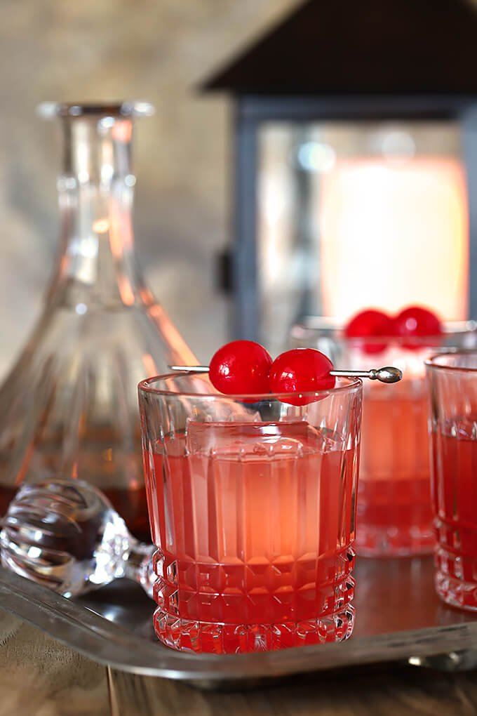Bourbon and Cherry Old Fashioned Cocktail Served in Glasses with Maraschino Garnish