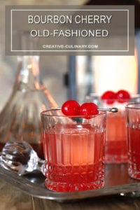 Bourbon Cherry Old Fashioned Cocktails with Maraschino Cherry Garnish in Setting with Cocktails and Decanter