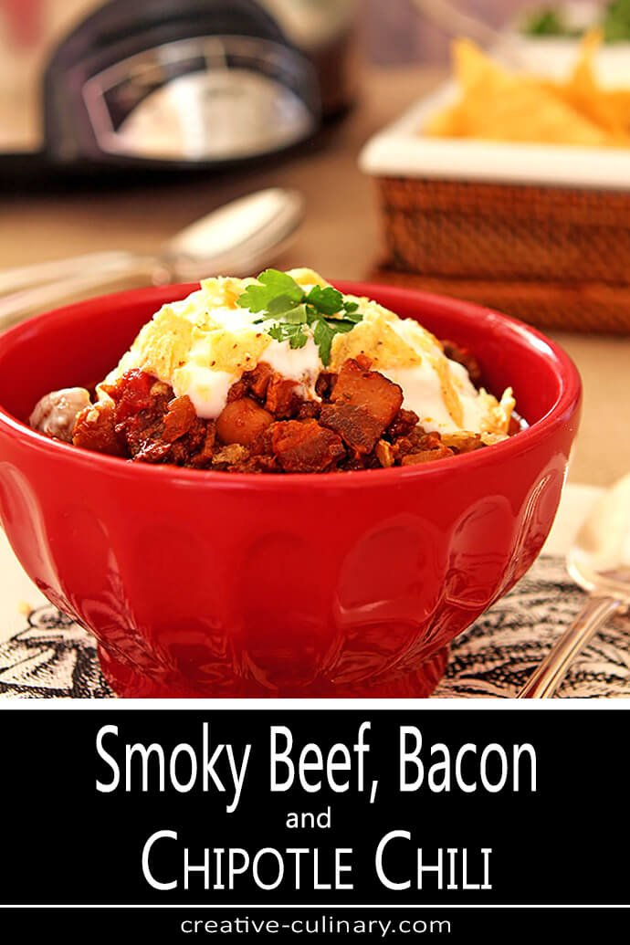 Smoky Beef, Bacon, and Bourbon Chili Served in a Red Bowl with Tortilla Chips and Sour Cream