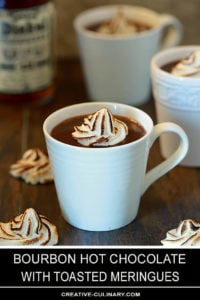 Bourbon Hot Chocolate with Toasted Meringue in a White Pottery Cup with Bourbon in Background