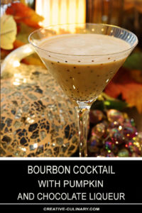 Bourbon Cocktail with Pumpkin and Chocolate Liqueur Served in a Gold Sparkle Martini Glass in Front of Sparkling Holiday Decor