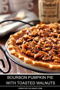 Whole Bourbon Pumpkin Pie with Toasted Walnuts in a White Pie Plate with Wrought Iron Holder