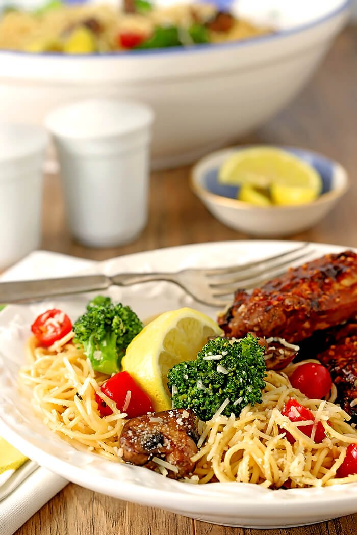 Pasta with Broccoli, Tomato, Mushrooms, and Parmesan Cheese Served with Chicken on a White Plate with Lemon Garnish