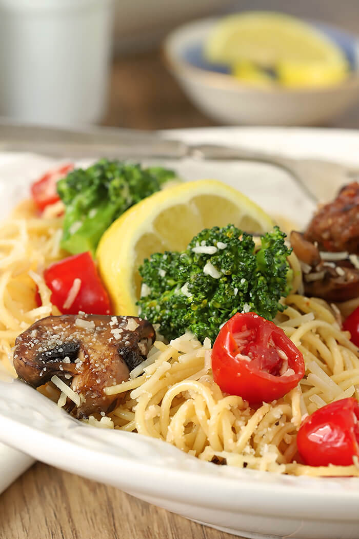 Closeup of Pasta with Broccoli, Tomato, Mushrooms, and Parmesan Cheese