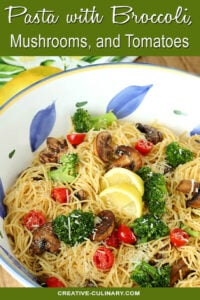 Pasta with Broccoli, Tomato, Mushrooms, and Parmesan Cheese in a Large White, Blue and Yellow Pasta Bowl
