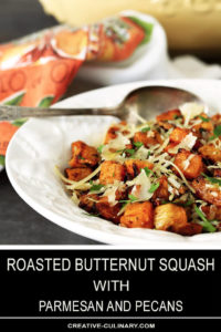 Roasted Butternut Squash with Pecans and Parmesan in a White Bowl with Serving Spoon and Peach Napkin