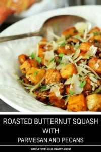 Roasted Butternut Squash with Pecans and Parmesan in a White Bowl with Serving Spoon