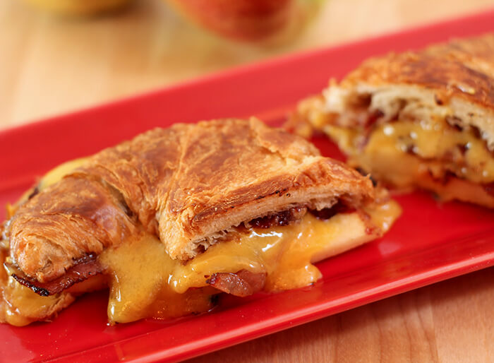 Cheddar, Pancetta, and Apple Grilled Cheese on Croissant Served on a Red Ceramic Tray